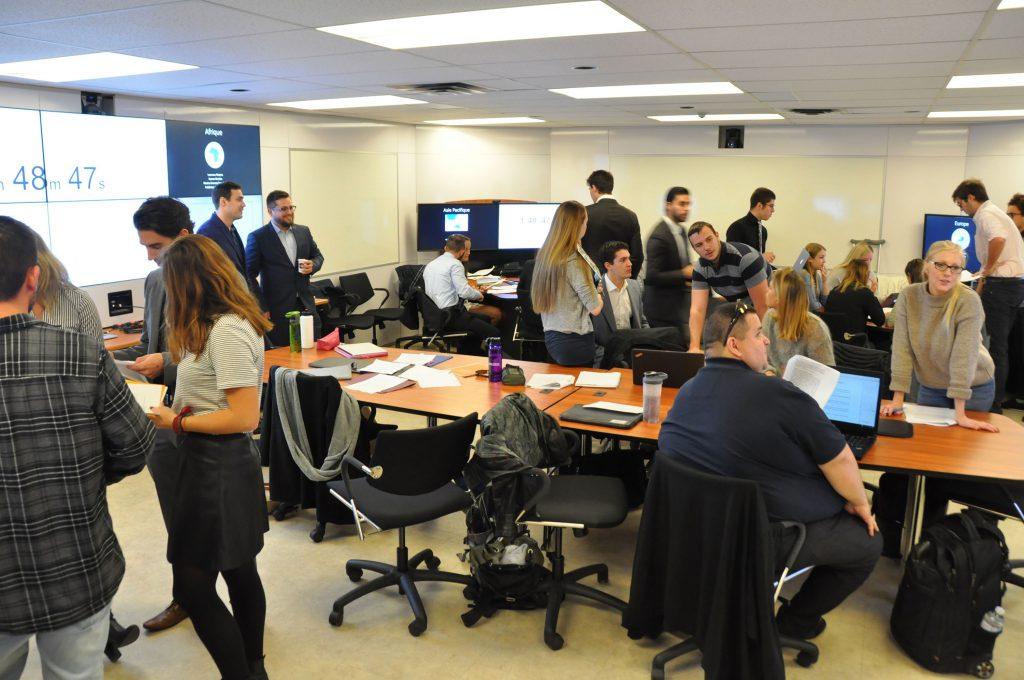 Un groupe d'étudiants et d'étudiantes sont en pleine action et discutent à différentes tables les différentes dispositions du traité.