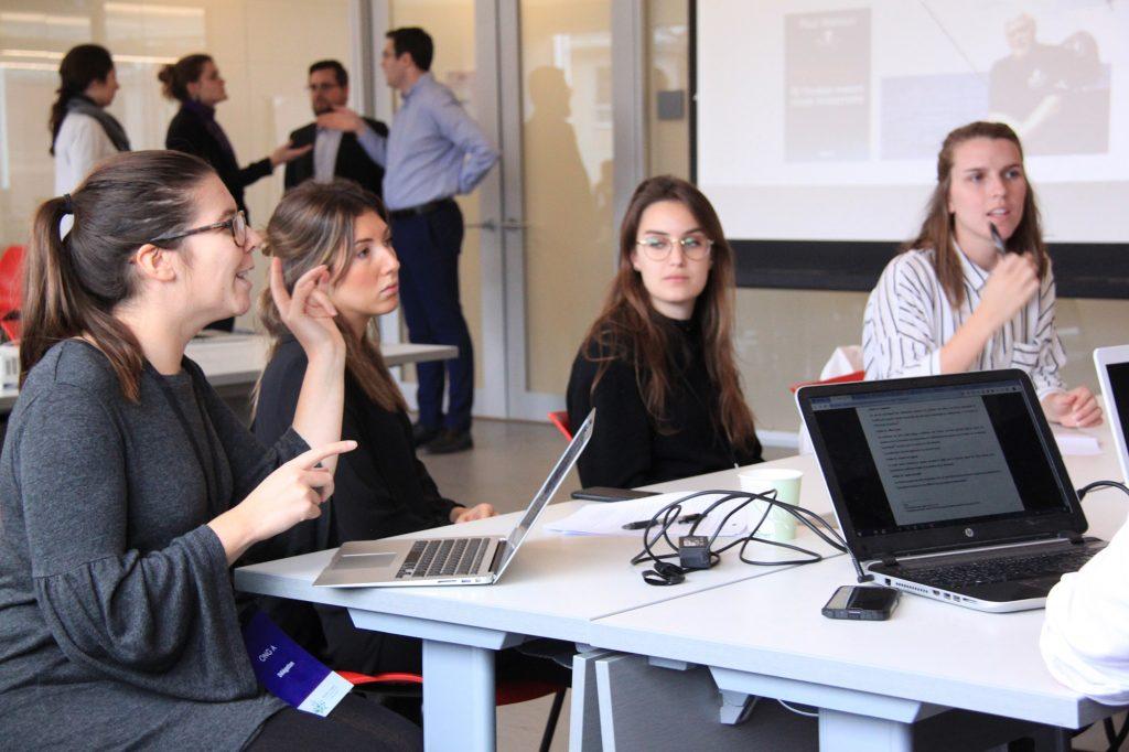 Un groupe d'étudiantes débattent devant un écrans projetant un fil d'actualité et utilisent leurs ordinateurs pour faciliter les discussion.